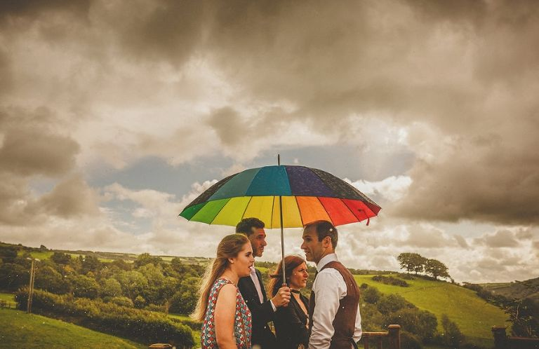 Wedding guests wait under a multi coloured umbrella in a field at Little Quarme Cottages