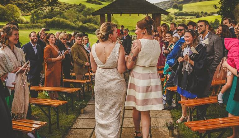 The wedding couple walk down the aisle together for the outdoor wedding ceremony at Little Quarme Cottages