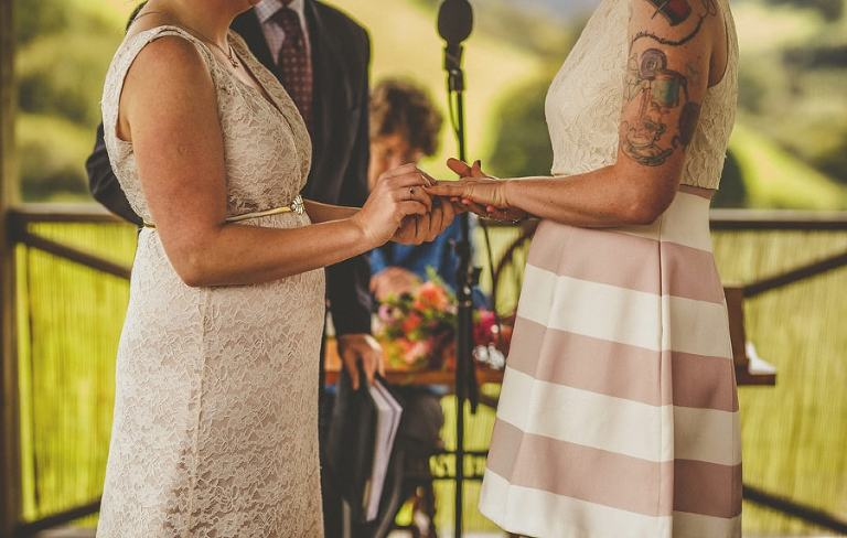 The bride places a wedding ring on the brides finger during the wedding ceremony