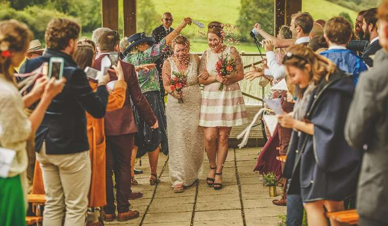 Confetti lands on the wedding couple as they walk down the aisle together at Little Quarme Cottages