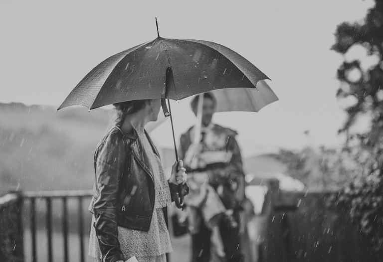 A wedding guest holds an umbrella over her head as the rain falls