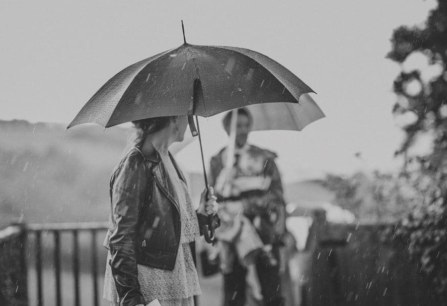A wedding guest holds an umbrella over her head as the rain falls