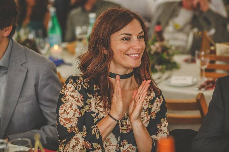 A wedding guest claps her hands as she sits at the wedding table in the outdoor marquee