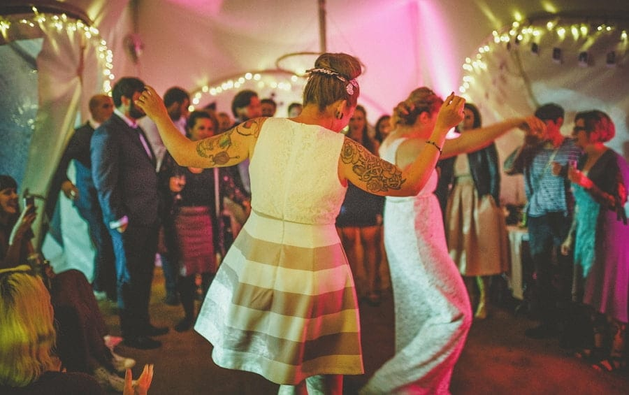 The bride and the bride dance together on the dancefloor in the outdoor marquee