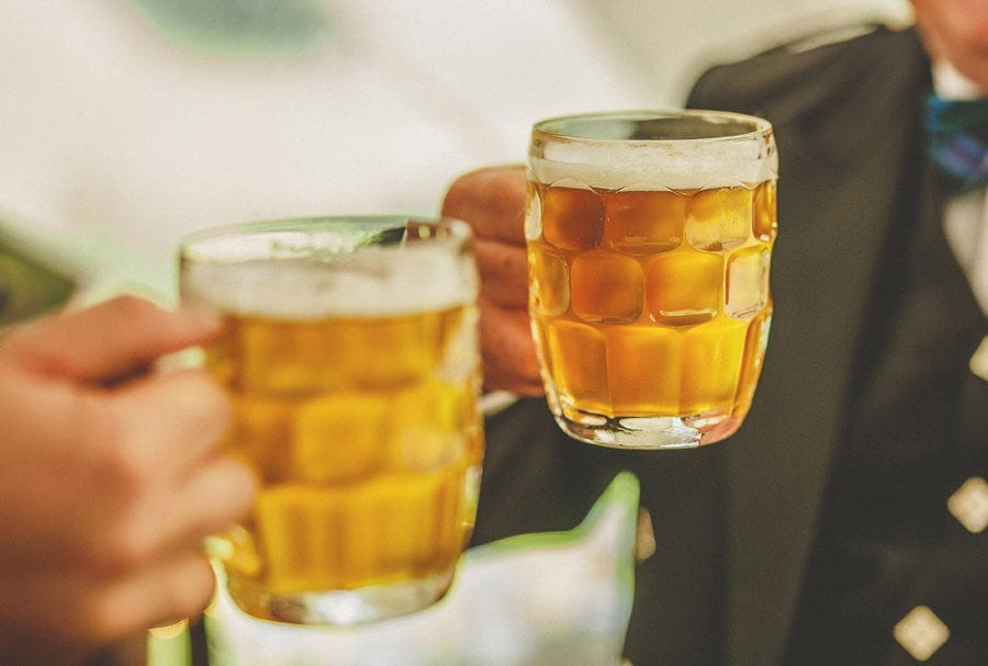Two wedding guests hold jugs of beer together