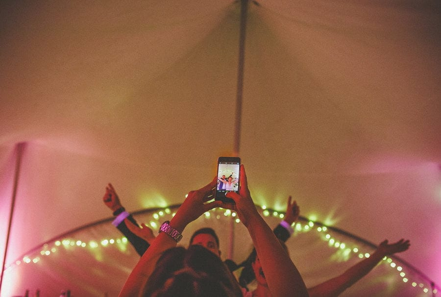 A wedding guest holds up a mobile phone and takes a photograph of people dancing in the outdoor marquee