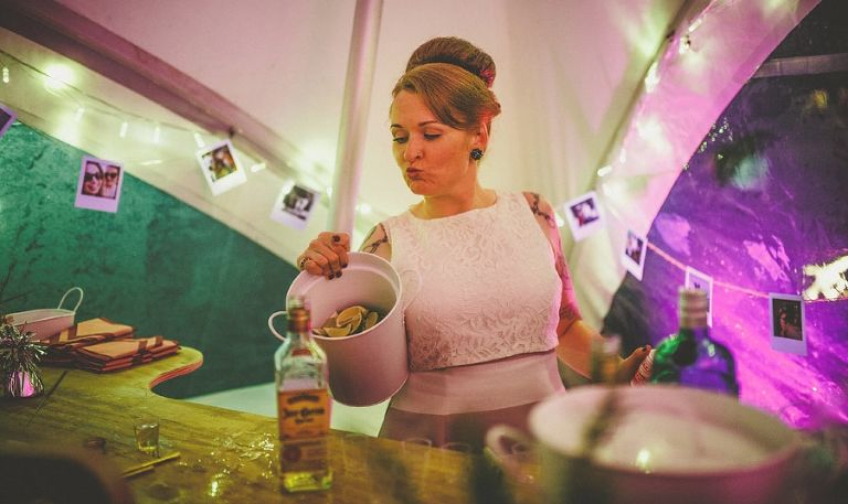 The bride holds a bucket of limes in her right hand behind the bar of the marquee