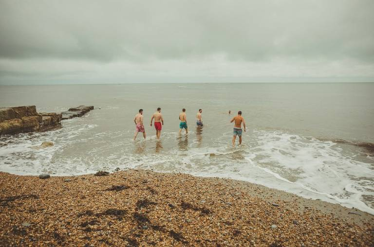 The groom and his ushers walk into the water on the pebbled beach at Lyme Regis in Dorset