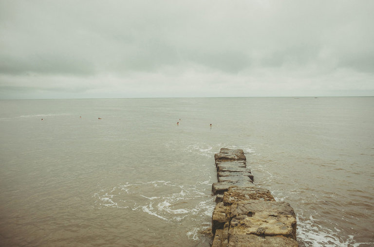 The groom and the ushers swim out to sea at Lyme Regis in Dorset