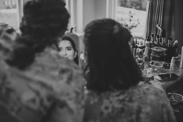The brides sister looks at herself as she holds up a hand held mirror