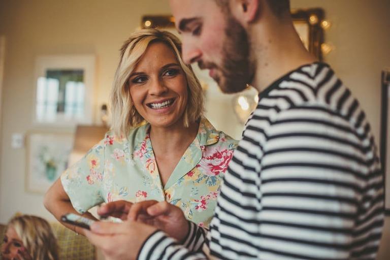 A bridesmaid smiles at a man looking at his mobile phone