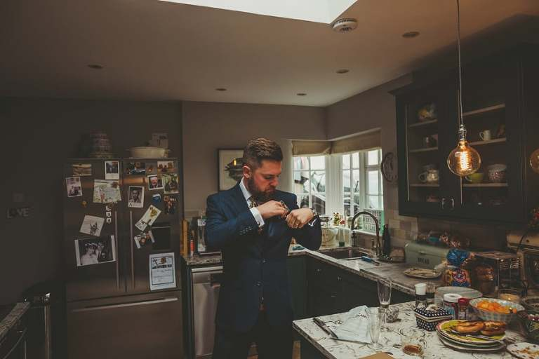 A man places a handkerchief into his suit pocket in the kitchen