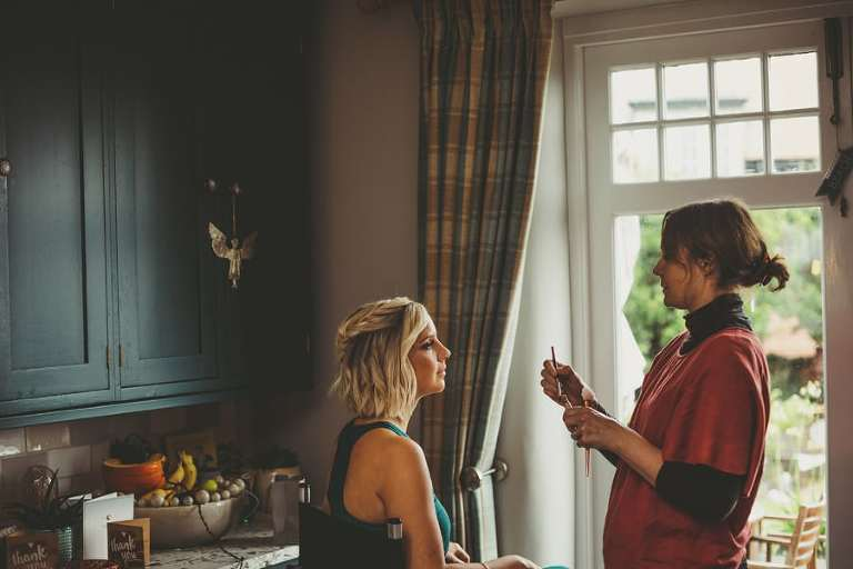 A bridesmaid sits next to a large window as the make up artist looks at her