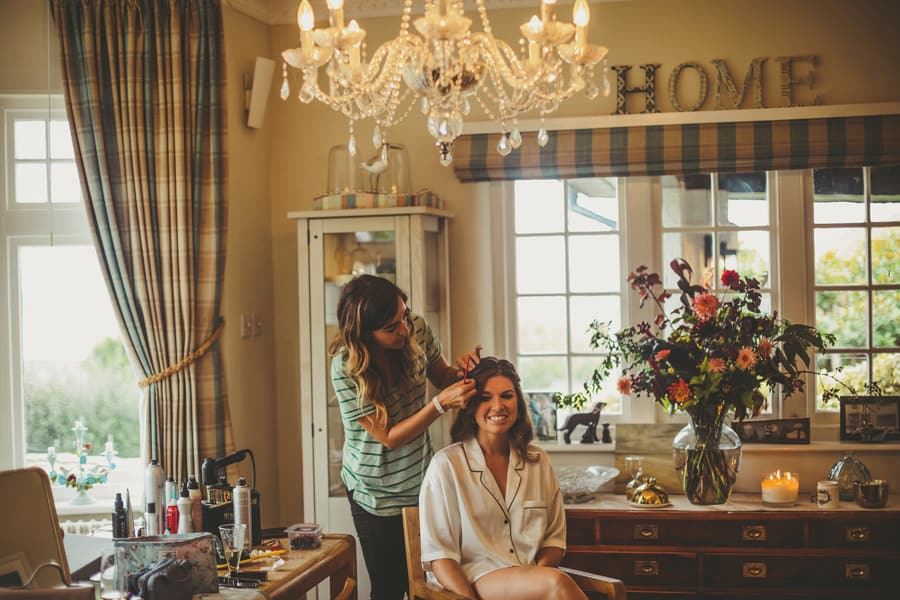 The bride sits down and has her hair tied back by the hairdresser