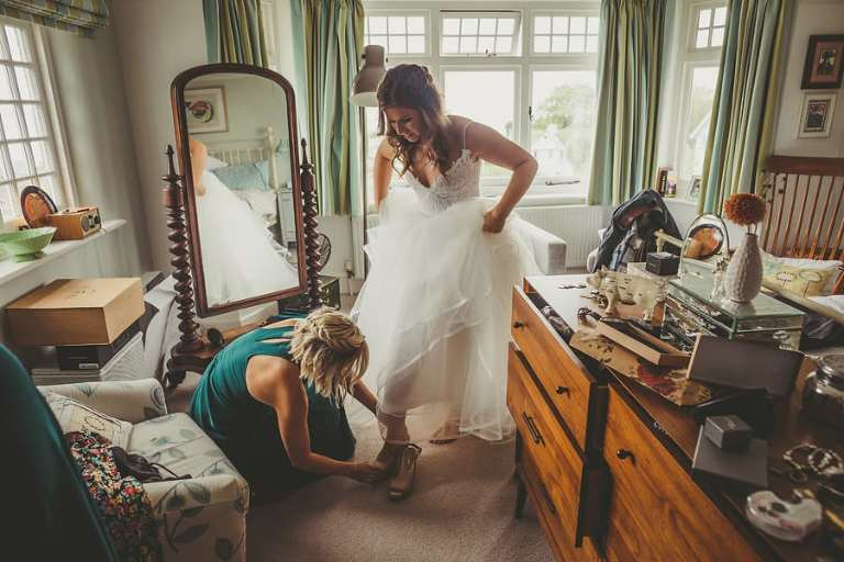A bridesmaid helps the bride put on her new shoes in her parents bedroom