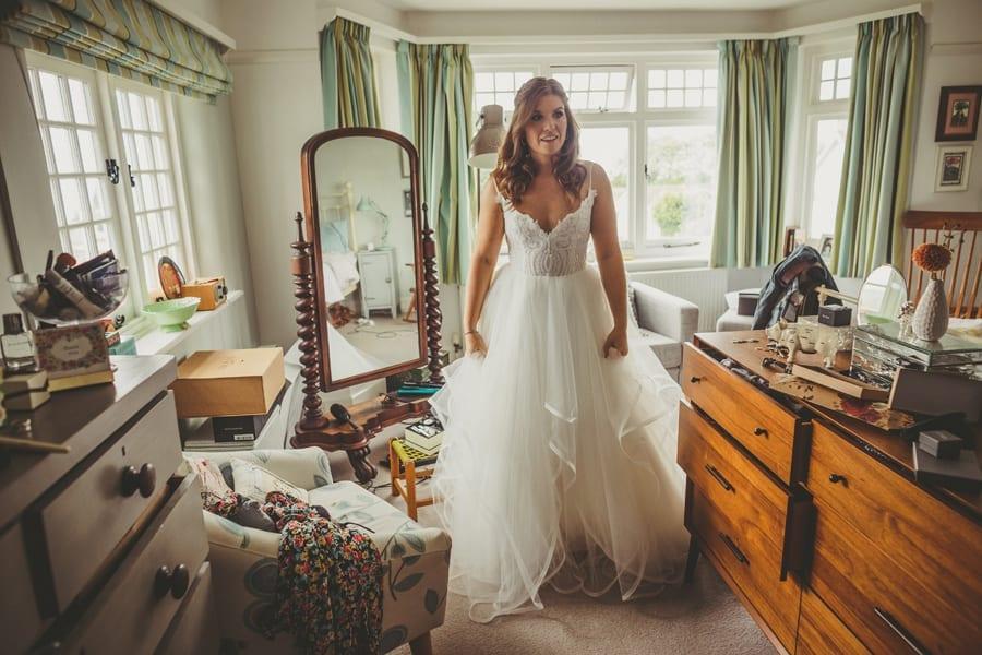 The bride stands in her wedding dress in her parents bedroom