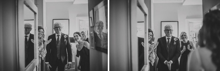 The bride's father looks at his daughter for the first time in her wedding dress