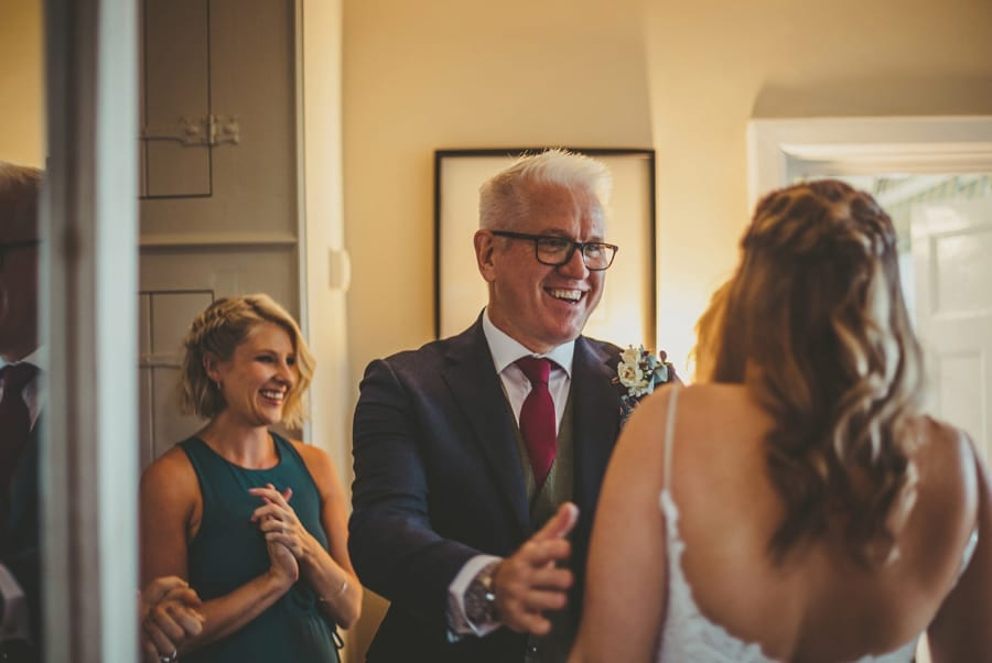 The bride's father puts his arms around his daughter and smiles at her