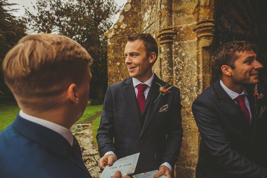The best man gives out an order of service to a wedding guest outside the Church