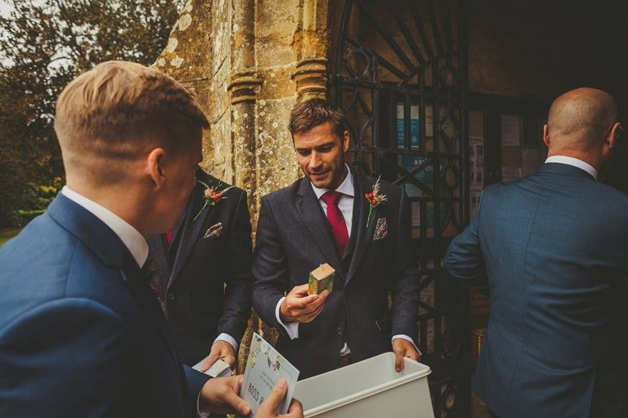 An usher hands a small box to a wedding guest outside the Church