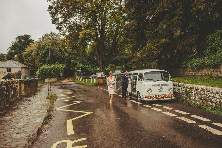 The brides mother walks away from the wedding car towards the Church