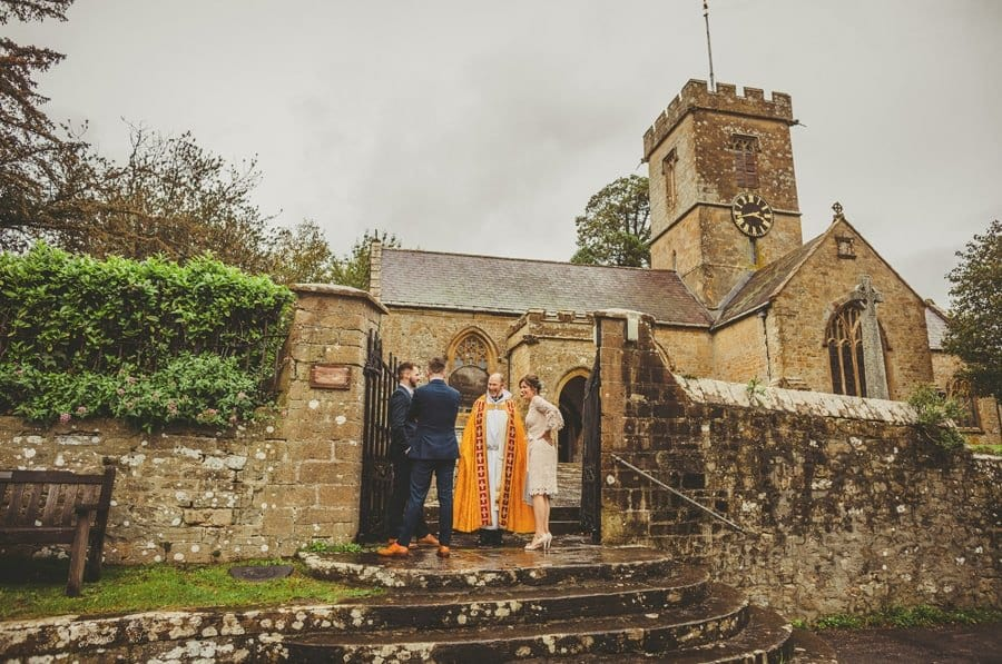 The vicar stands outside the Church and talks to the brides mother and the ushers