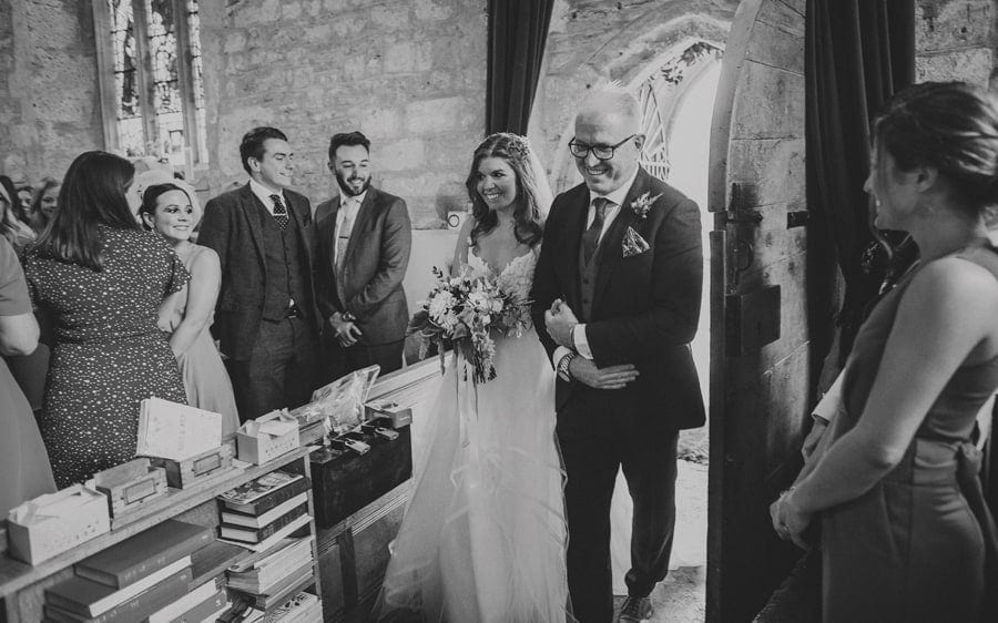 The bride and her father walk into the Church together