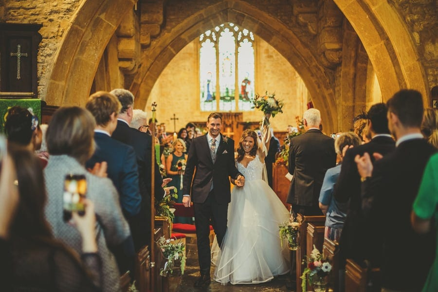 The bride raises her bouquet in the air as she holds the grooms hand in the Church