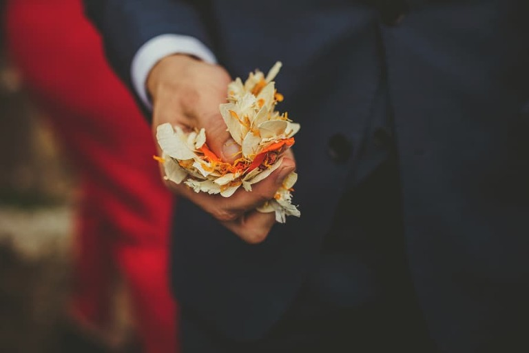 A wedding guest holds confetti in his hand