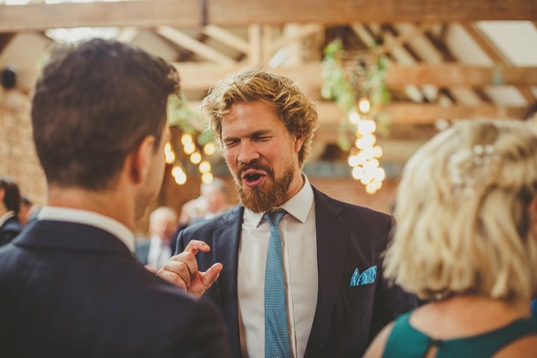 A wedding guest closes his eyes as he is talking