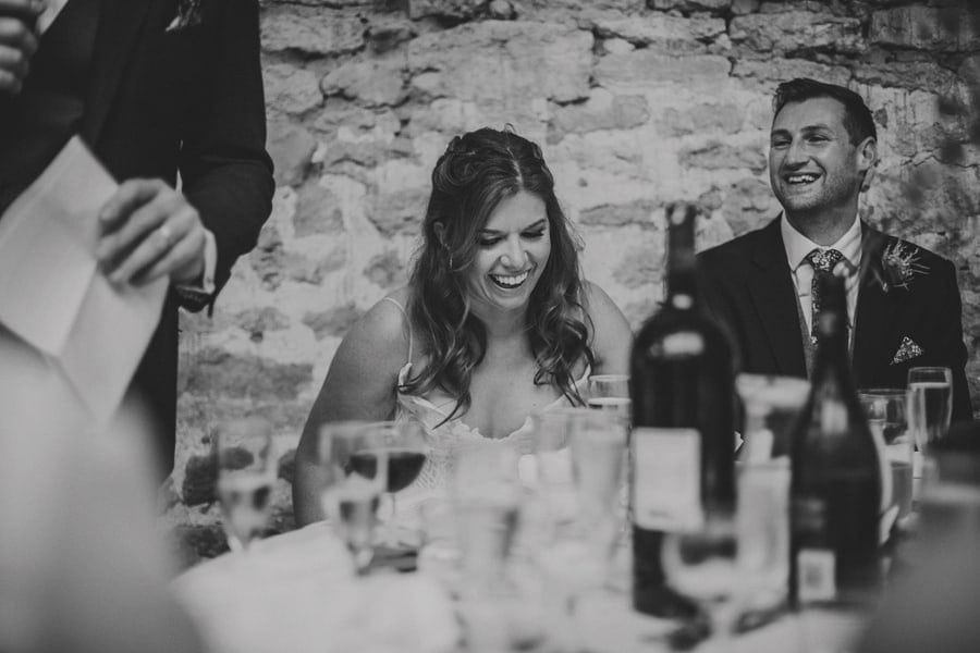 The bride sits at the table and laughs at her father's wedding speech