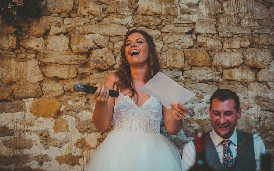 The bride stands up and speaks in front of the wedding guests with a microphone in one hand and a piece of paper in the other hand