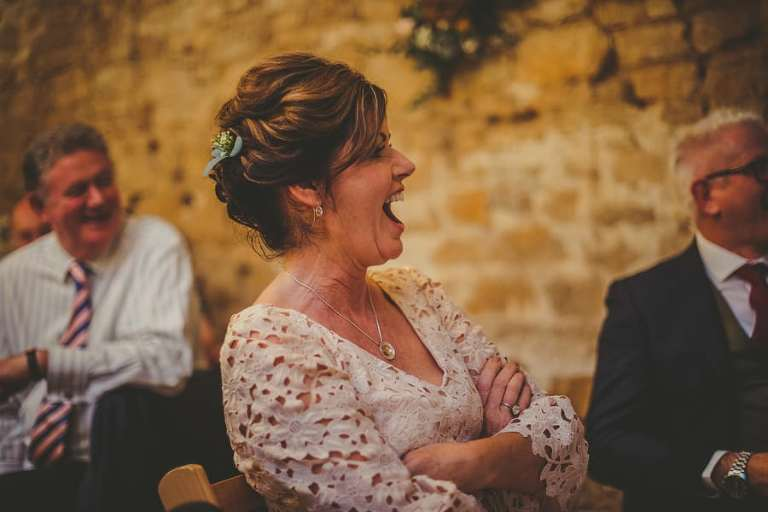 The brides mother laughs at the wedding table