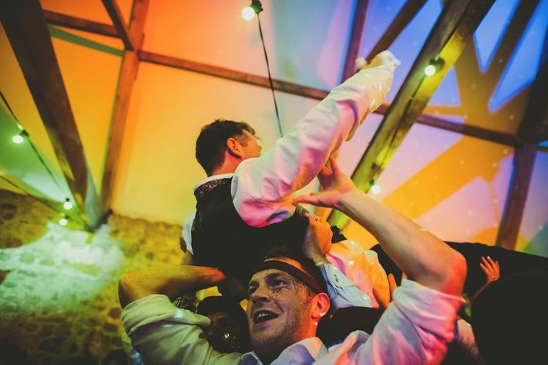 The ushers lift the groom over their shoulders