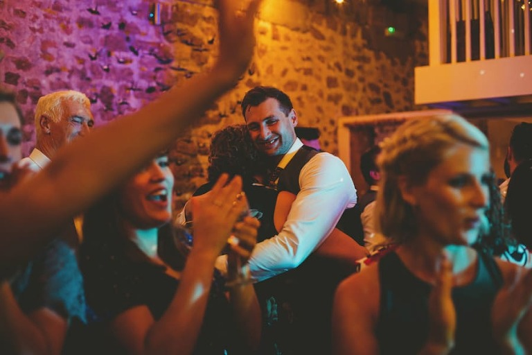 The groom puts his arms around his mother on the dancefloor