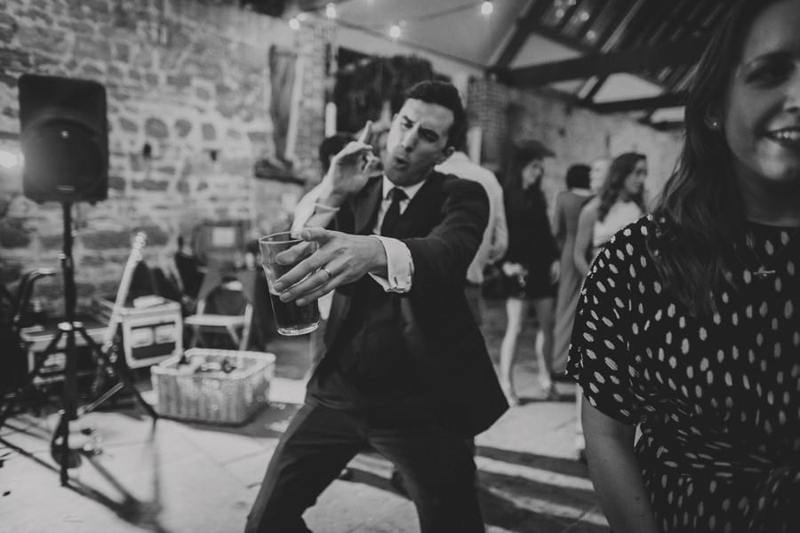 A wedding guest dancing with a drink in his hand