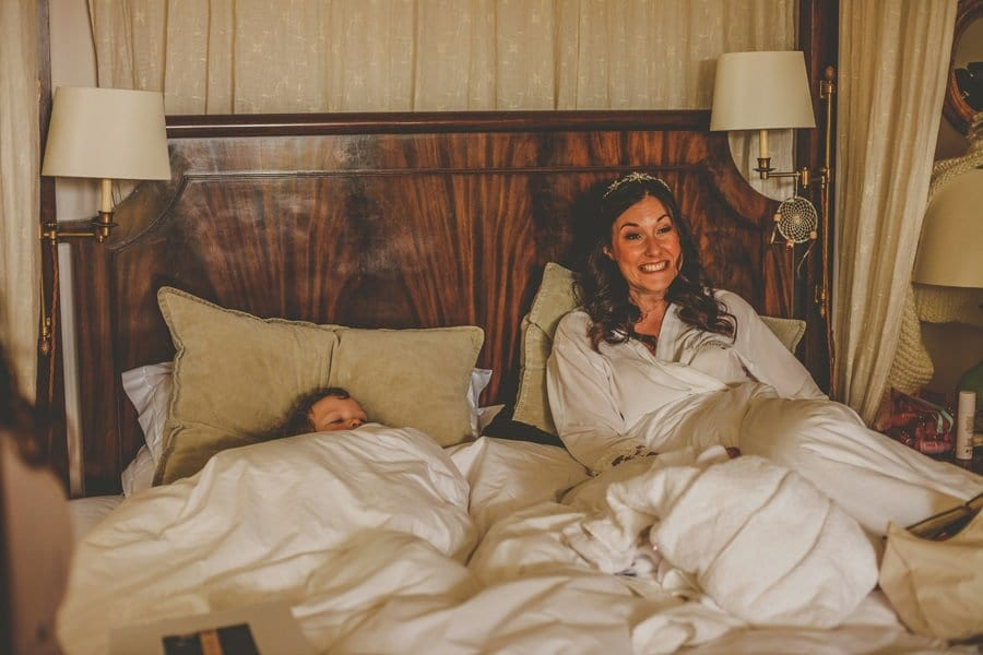 The bride sits in bed with her niece looking out under the covers