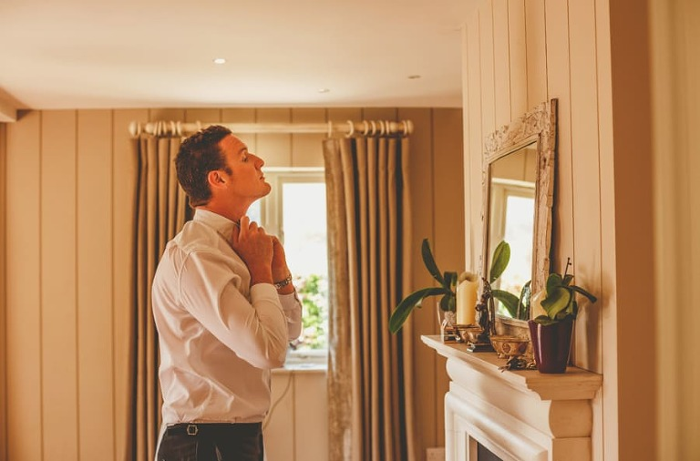 An usher straightens the collars of his shirt as he looks into the mirror hanging from a wall in the house