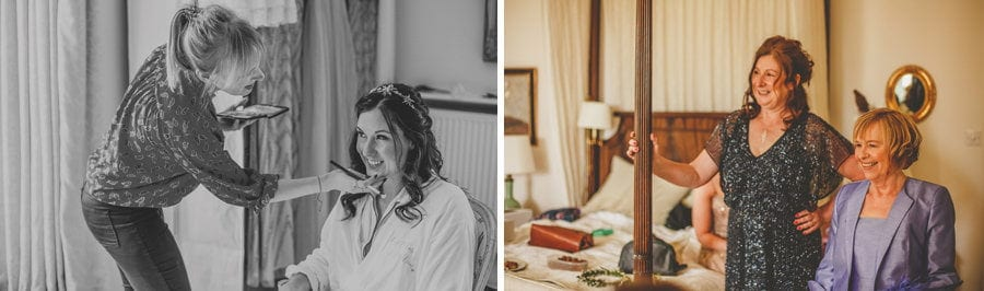 The make up artist applies makeup to the face of the bride who is sat on a chair looking out of a window