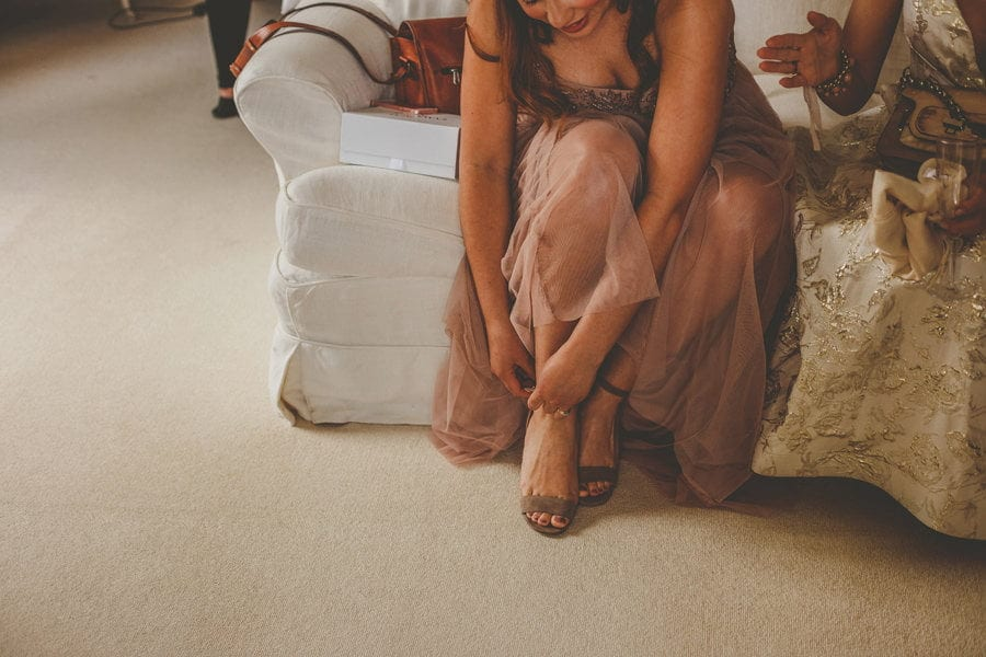 A bridesmaid sits on a sofa and fastens her new shoes