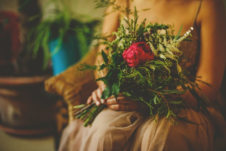 One of the bridesmaids sits down with her bouquet of flowers