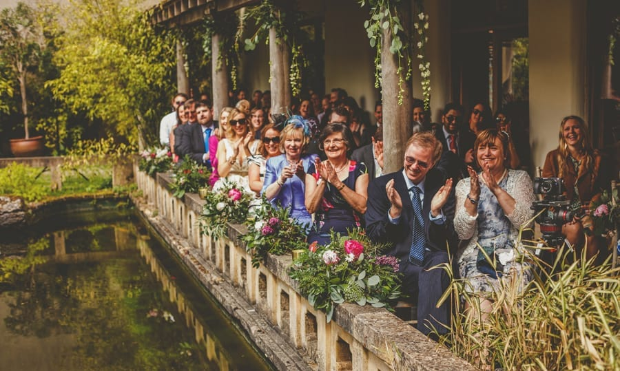 Wedding guests applaud the bride and groom during the wedding ceremony