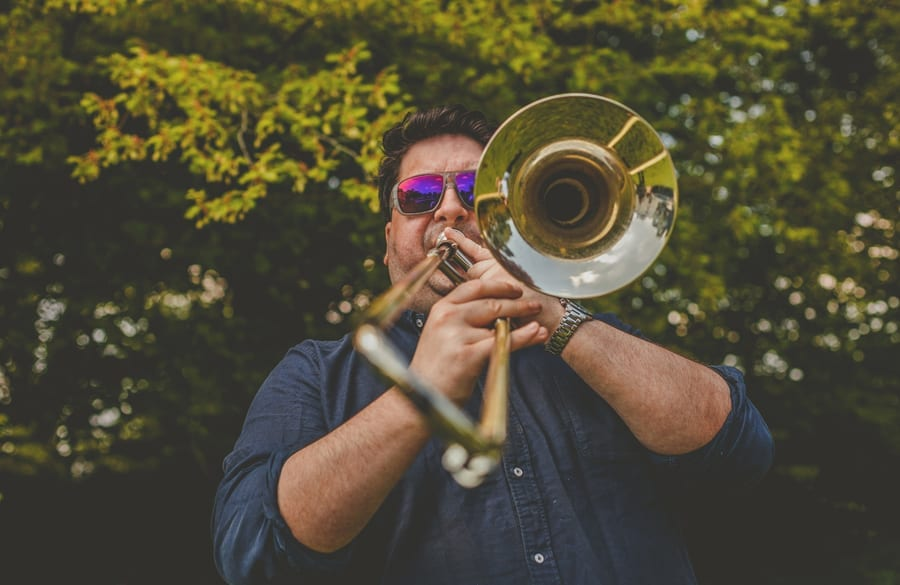 A member of the wedding band plays his instrument outside