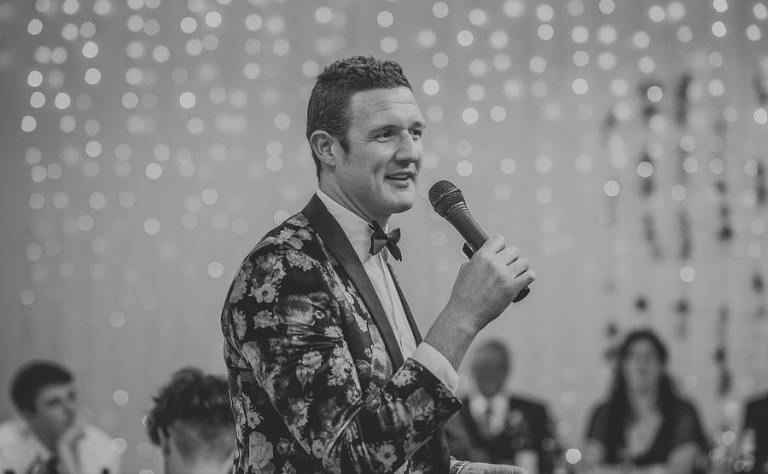 The best man speaks to the wedding guests using a microphone