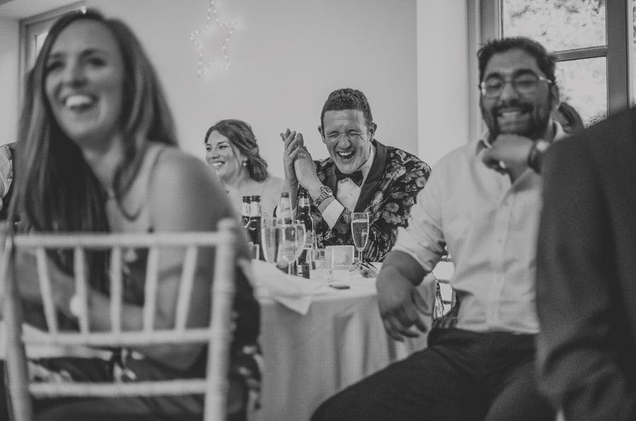 The best man laughs as he sits at a table with friends during the grooms speech