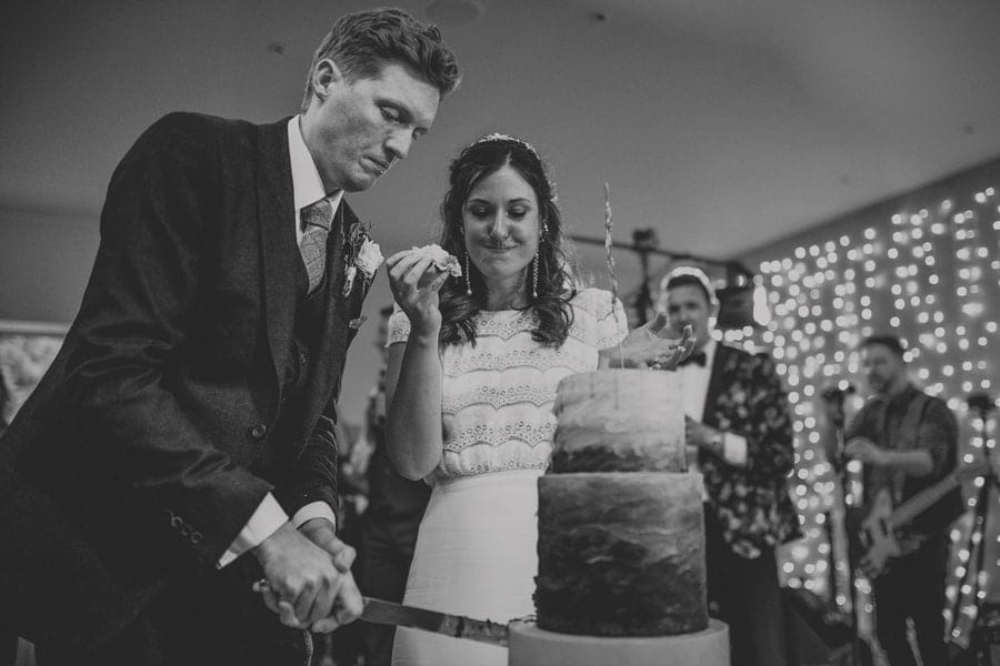 The bride puts a piece of wedding cake into her own mouth and watches her husband cut the wedding cake