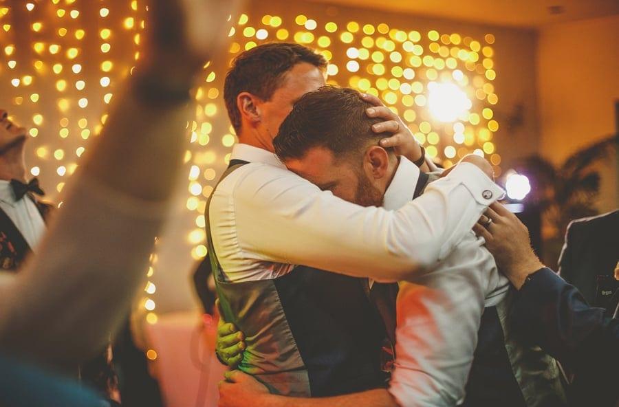 The groom hugs the best man on the dancefloor