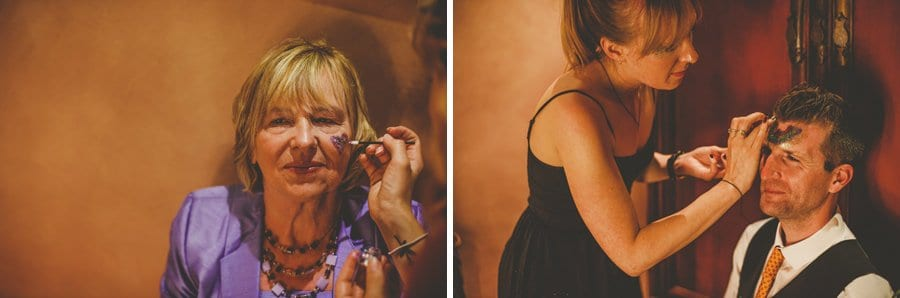 The make up artist paints glitter on the faces of the wedding guests