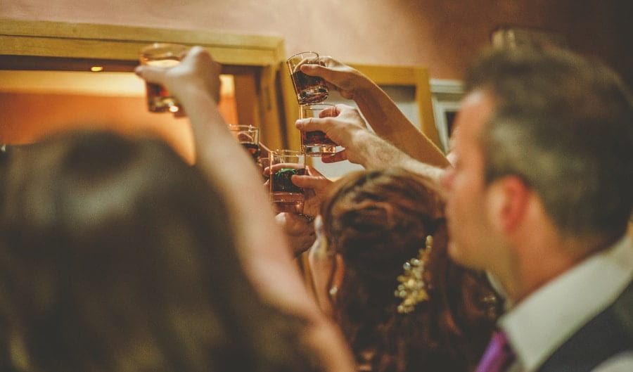 Wedding guests lift up their alcoholic drinks and congratulate the bride and groom