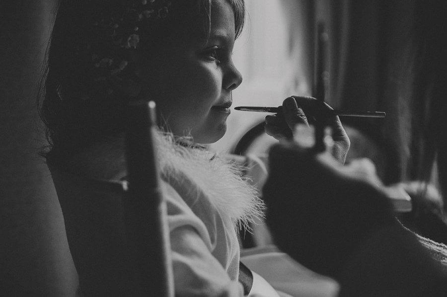 The make up artist applies lipstick on the flower girls lips